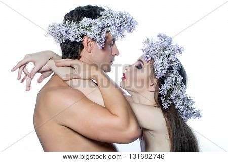 Young man and beautiful woman in lilac wreathes hug with love naked isolated on white background