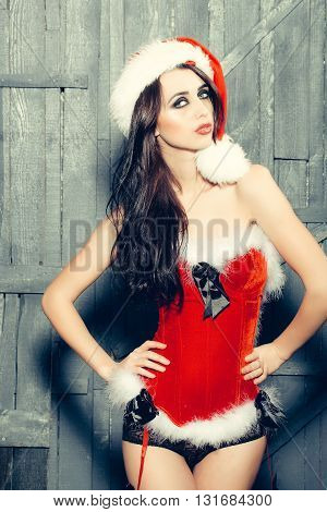 Attractive woman in Santa Claus corset and red hat in studio on wooden background