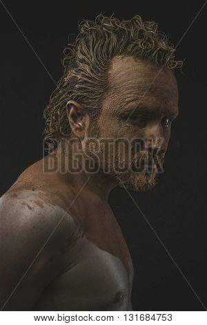 Dirty, covered with mud all over her naked body on black background man. adventure and risk, competition force
