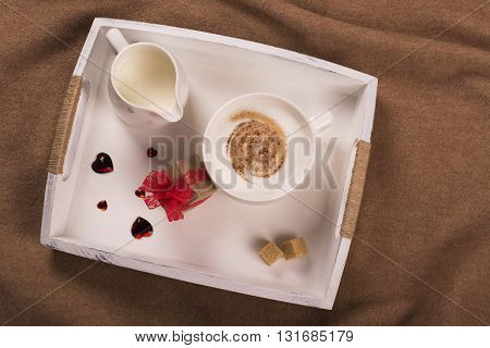 Cozy morning concept. Cup of cappuccino and small gift box on wooden tray. Top view
