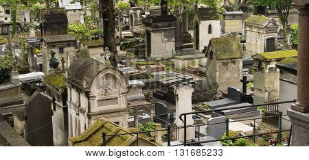Old and ancient moss covered stone Crypts and Tombstones in a Graveyard in Europe