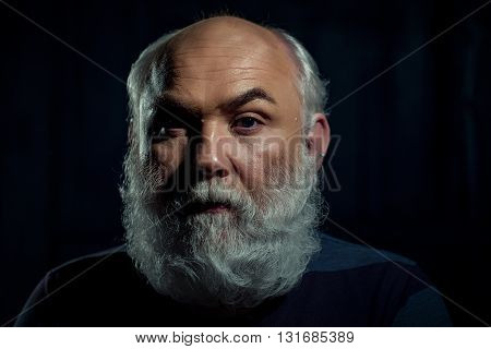 Old man with long white beard and moustache on serious face in studio on black background closeup