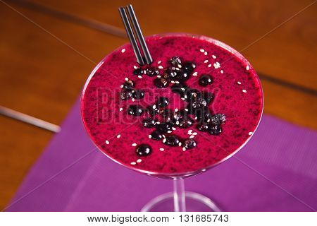 red currant smoothie in tall glass on violet background