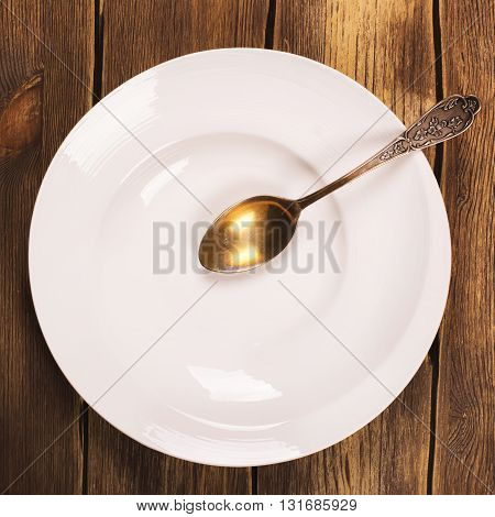 Top view of white empty plate with vintage spoon over grunge wooden table. Toned image