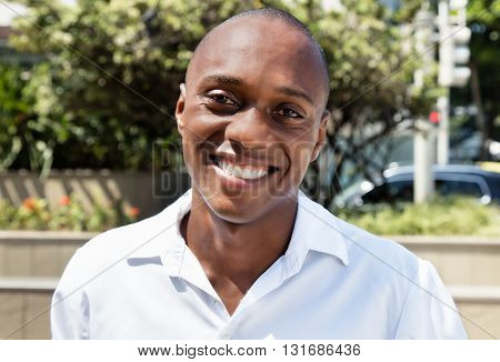 Laughing african american man in white shirt outdoor in the city in the summer