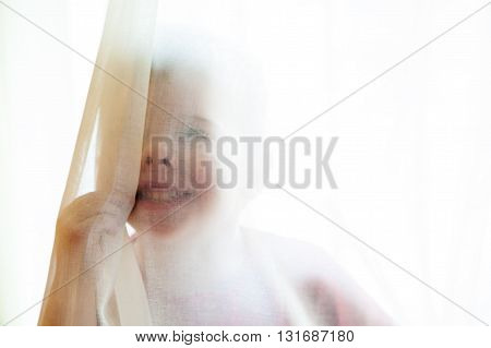 A little boy smiles behind sheer curtains as he presses his nose up on them smashing it a bit. The image is backlit soft and sheer.