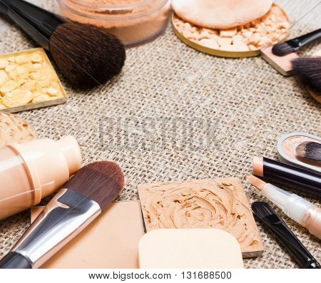 Makeup products to even out skin tone and create the perfect complexion laid out as frame on sackcloth. Foundation, concealers, various types of powder. Side view, shallow depth of field. Copy space