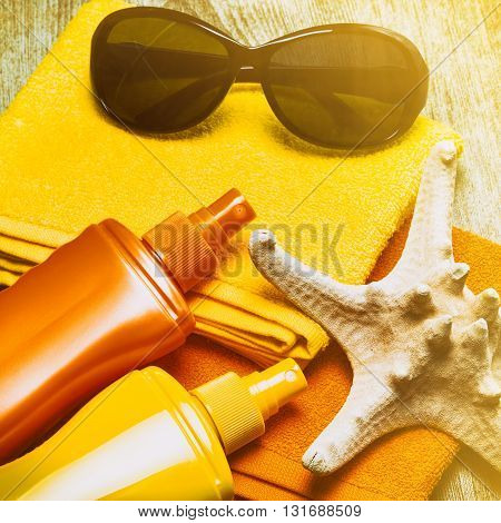 Cosmetic sunscreen products, starfish, sunglasses and towels on wooden planks. Skin care cosmetics containing sun protection factor. Retro style processing