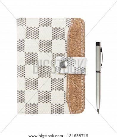 brown leather notebook with a pen on a white background; Leather notebook and pen isolated on the white background