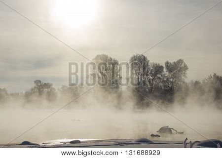 foggy winter landscape frosty morning over the river and trees in hoarfrost on the shores of
