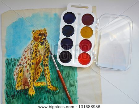 I have drawn on a sheet of paper drawing of a cheetah using watercolor paints and brushes.