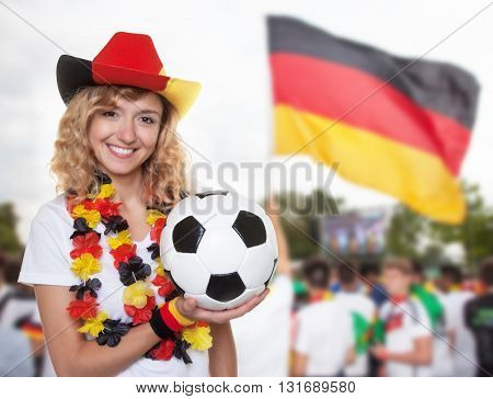 Laughing woman in german jersey with ball and other fans in the background