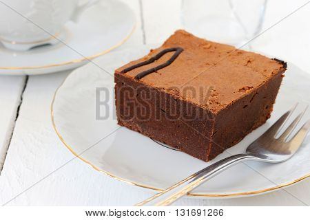 a piece of chocolate cake and a cup of coffee; shallow depth of field