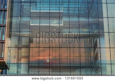 Modern blue glass wall of an office building in the background a sunset.