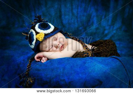 A sleeping newborn boy takes a catnap while an crocheted owl hat.
