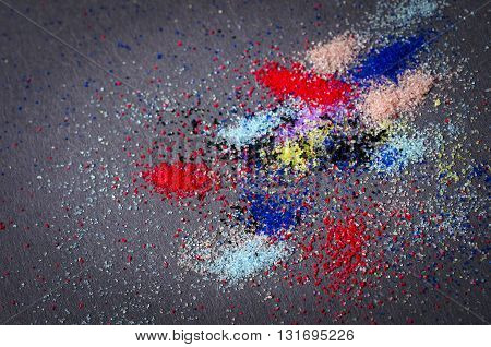 many colored powder paint makeup artistry abstract scattered on a black background