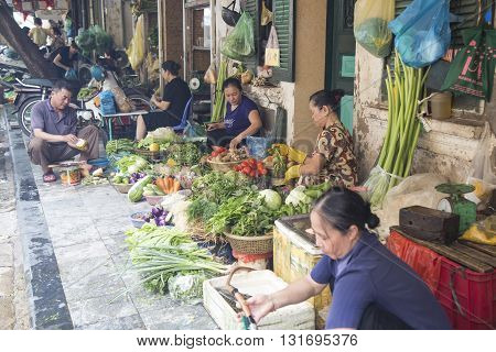 Hanoi, Vietnam - May 28, 2016: Vietnamese vendor selling vegetable and other tropical agriculture products at a flea market on the side walk of an old street in Hanoi capital.
