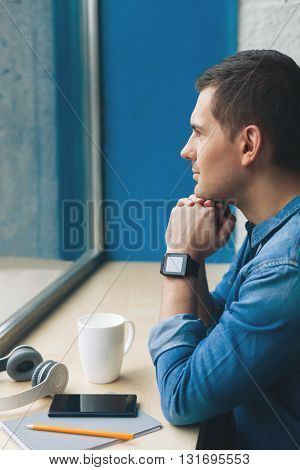 Attractive young man is relaxing and dreaming. He is looking through the window with inspiration. The man is sitting at windowsill with cup and mobile phone