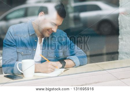 Attractive young man is writing with inspiration near a window. He is sitting and smiling. There are cup of coffee and mobile phone on windowsill