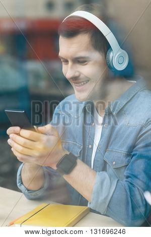 Cheerful young guy is using a mobile phone and smiling. He is listening to music from headphones. The guy is sitting near the window