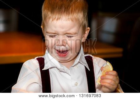 A little boy makes an awful face after tasting a sour lemon.