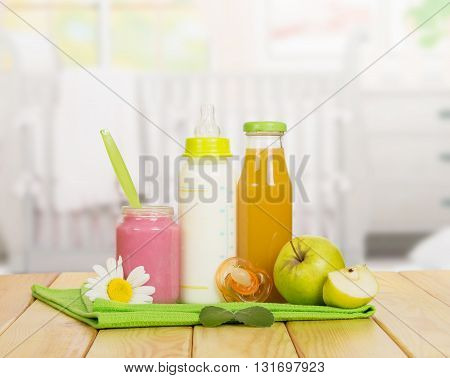 Bottles with milk and juice, fruit puree jar, soother and towel on a background of the kitchen.