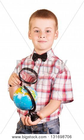 Cheerful, cute schoolboy holding a magnifying glass and globe isolated on white background.