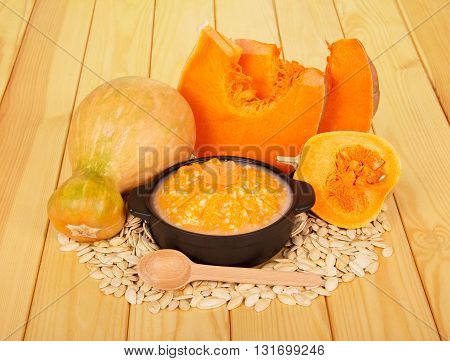Slices of pumpkin porridge, seeds and spoon on a background of light wood.
