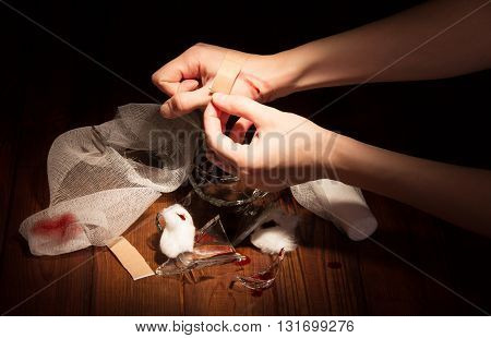 Fragments of broken glass, a wounded arm, patch and bandages isolated on a black background.
