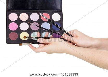 Palette of colorful eye shadow, cosmetic brushes in female hands isolated on white background.