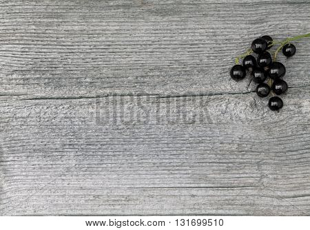 Black Currant in closeup on an elderly wooden board, plank. Texture, pattern in the board.