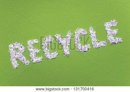 tilted recycle word made from heap of shredded white paper over bright green background