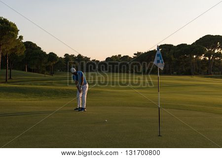 golf player hitting ball  with driver on course at beautiful sunset