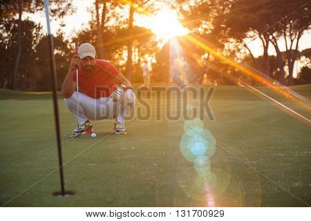 golf player aiming shot with club on course at beautiful sunset with sun flare in background