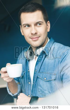 Attractive young guy is drinking a cup of coffee. He is standing and looking aside with interest