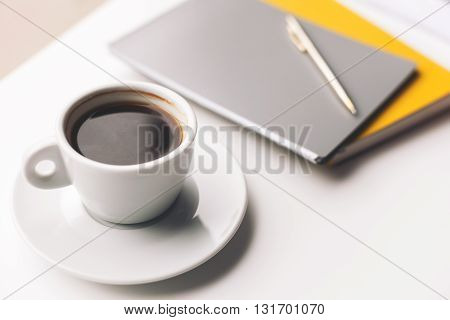 Close up of cup of coffee near notebooks on table