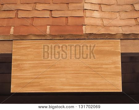 Blank wooden signboard hanging on wood roof. Wooden board old-style. Wood sign board.