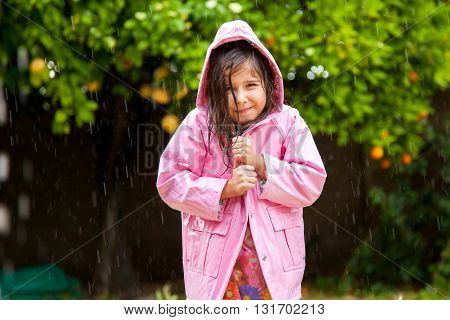 A sweet little girl pulls her pink raincoat closed as she stands happily in a Spring shower.