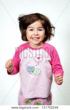 An excited girl jumps up and down in front of a white background. Her hair is bouncing and she has a big grin and big expressive brown eyes. She is wearing pajamas.
