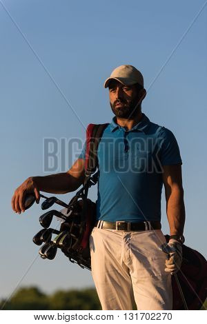 handsome middle eastern golfer portrait at golf course at beautiful sunset