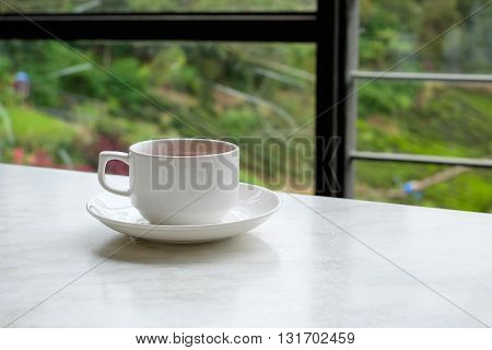 White cup of tea on white marble table in tea shop at Cameron Highlands Malaysia.