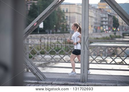 sporty woman running on sidewalk at early morning with city  sunrise scene in background