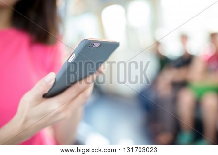 Woman use of mobile phone inside train compartment