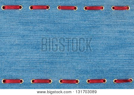 Fashionable background red satin ribbon inserted in denim with space for your creativity