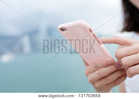 Woman checking information on cellphone beside Victoria harbor in Hong Kong