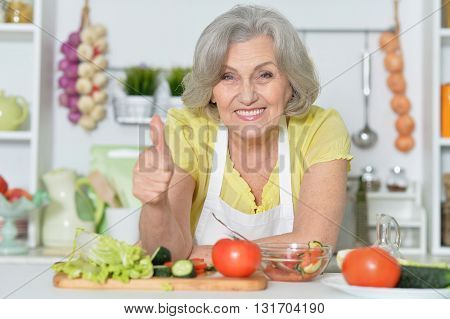 Senior woman with grey hair cooking in kitchen with thumb up