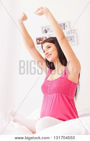 Cute young pregnant woman is stretching arms after waking up. She is sitting on bed and smiling