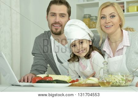 portrait of happy family cooking  in kitchen with laptop