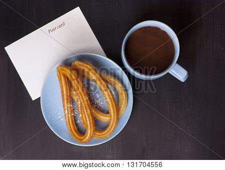 Plate of churros traditional Spanish (and especially Madrid) dessert (especially for Sunday breakfast) with cup of hot chocolate with blank postcard with copyspace on dark black wooden tabletop