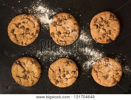 Two rows of freshly baked chocolate chips cookies with flour shot from above on an old black baking tray